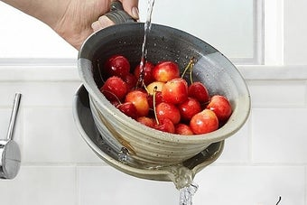 Hand tilting the strainer into the sink to drain water out as cherries sit inside the deep bowl
