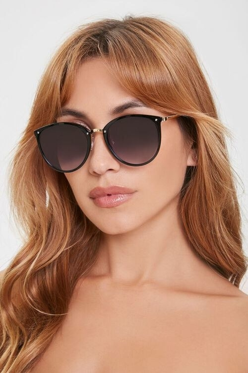 Model in black round sunglasses with gold accents