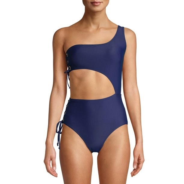 Model in asymmetrical one-piece with side lacing