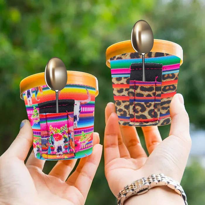 A pair of hands holding two small tubs of ice cream dressed in the neoprene cozies