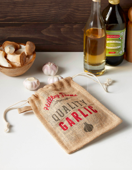 A jute garlic bag on a kitchen counter with several heads of garlic peeking out