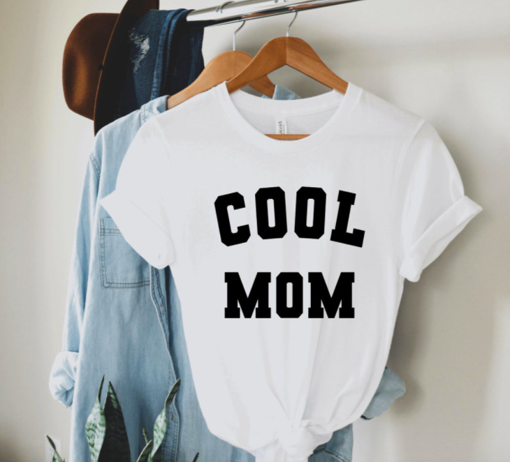 A simple tee shirt hung on a rack with the words cool mom printed on the front in large block letters