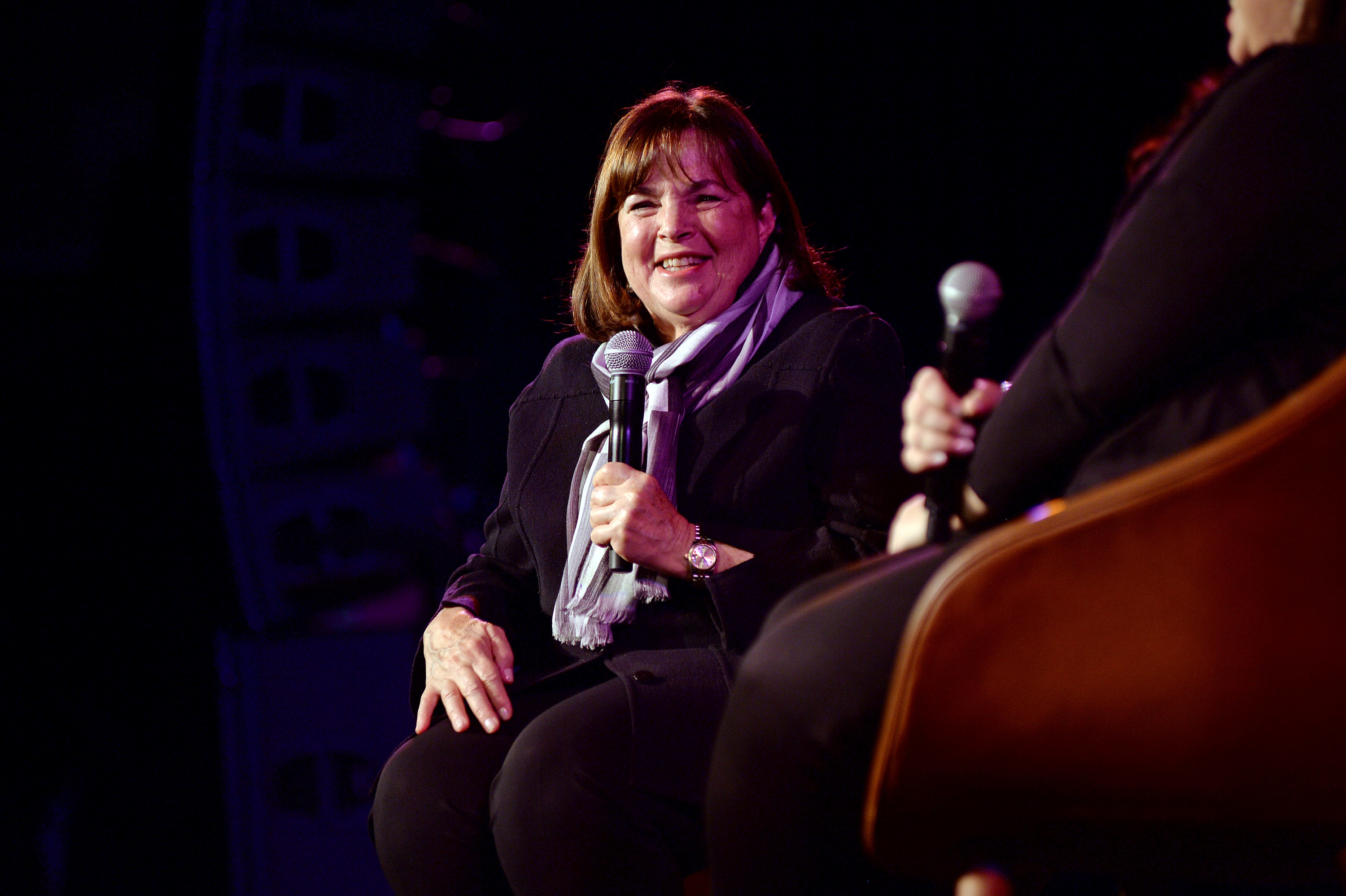 Ina Garten sitting in a chair onstage holding a microphone and doing an interview