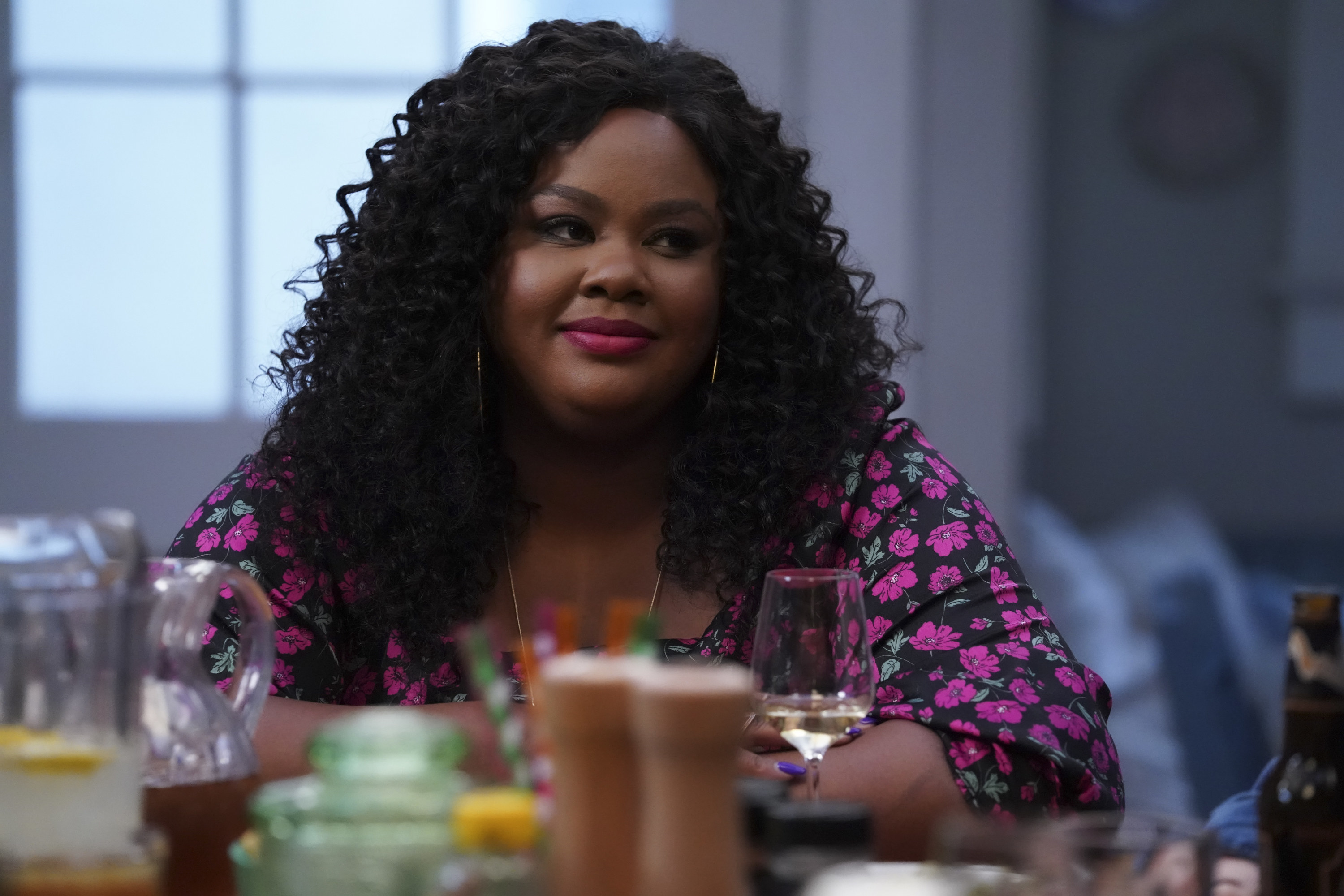 Nicole Byer sitting at a table with a glass of wine