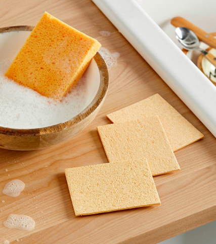 A trio of flat dish sponges next to a bowl of soapy water