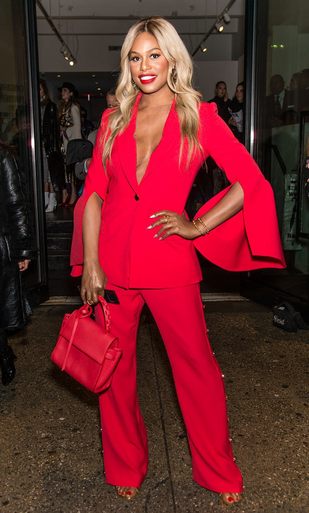 Laverne in a monochrome suit with a long jacket with a deep v buttoned and long sleeves that flare at the elbow with a cutout and pants that have studs on the sides