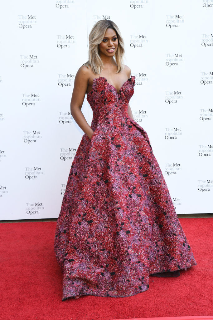 Laverne in a bright floral flare ballgown with a structured strapless top that juts out from her body in petal-like pieces at the top