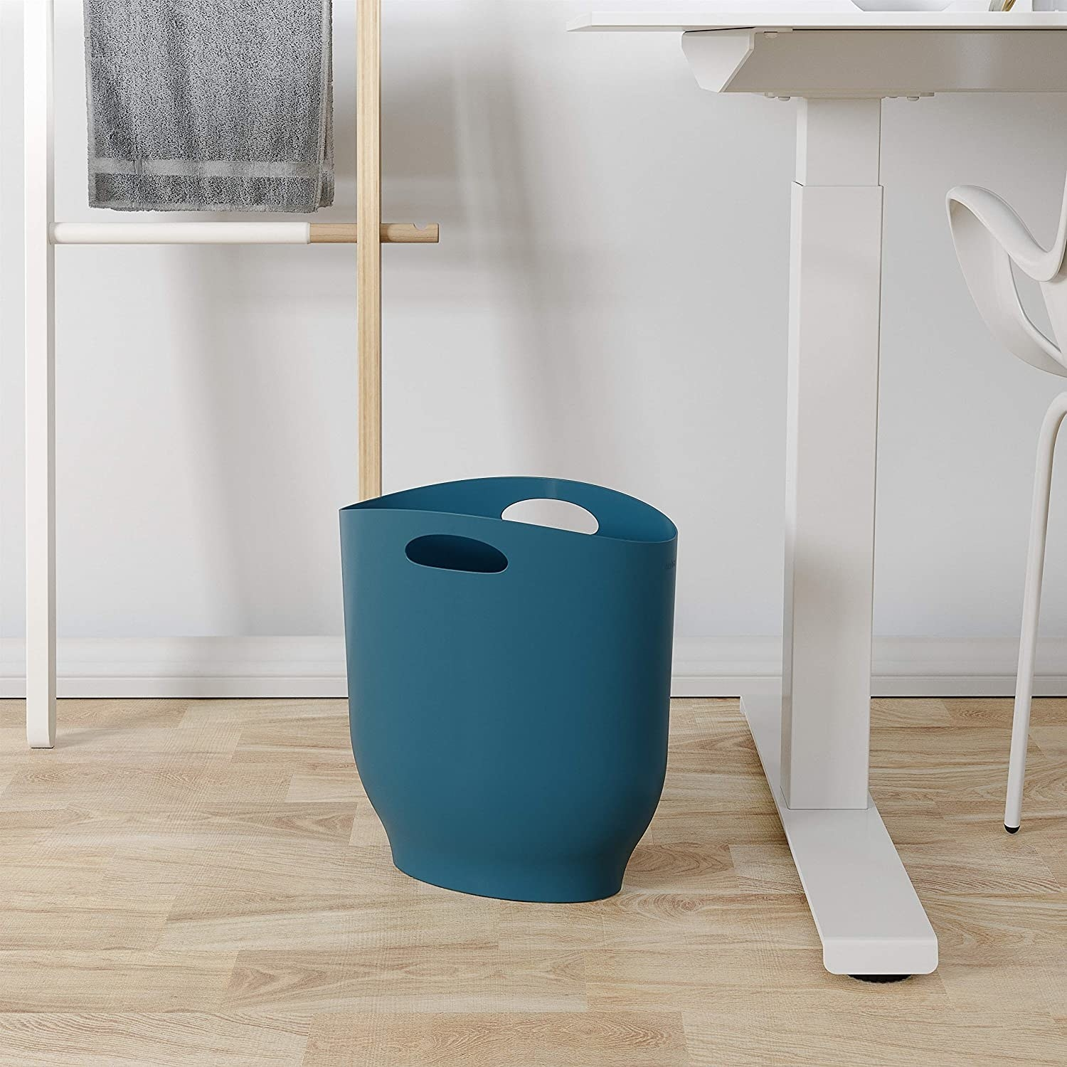 A slim trash can next to a modern desk