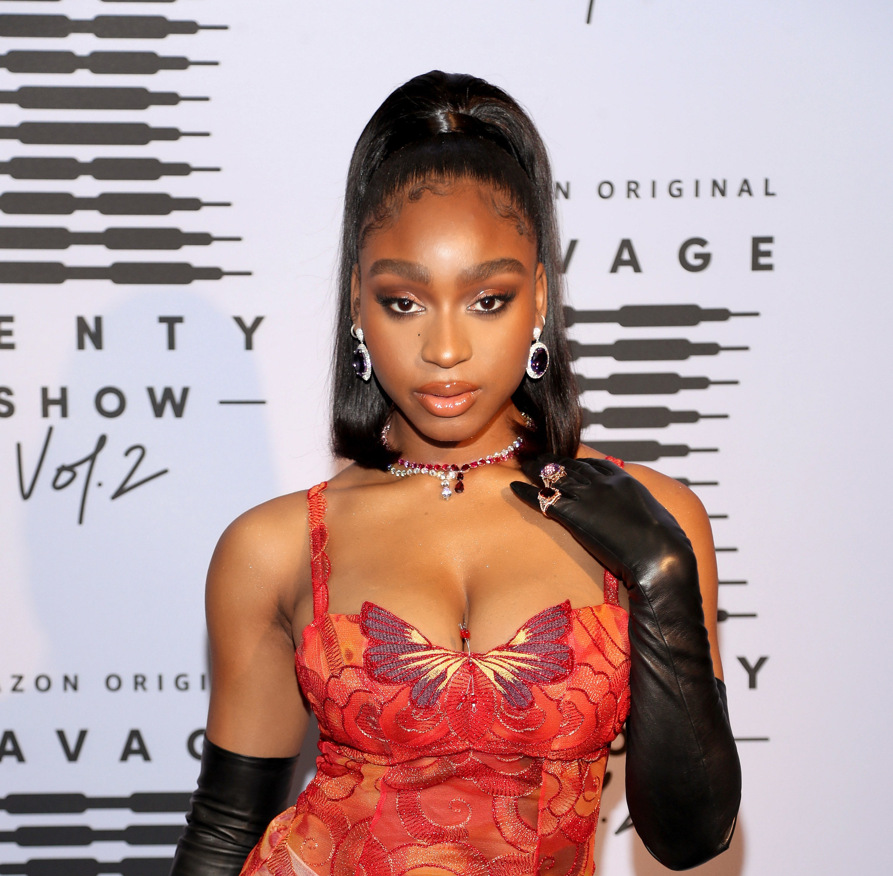 Normani on a red carpet with a red top and long black leather opera gloves