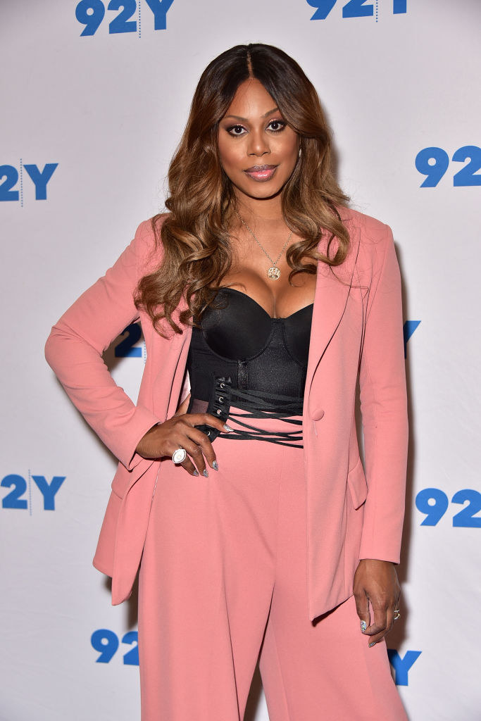 Laverne in a loose suit with a long suit jacket that's open and matching loose high waist pants with a short sweetheart neckline corset underneath with lacing connecting it to the pants