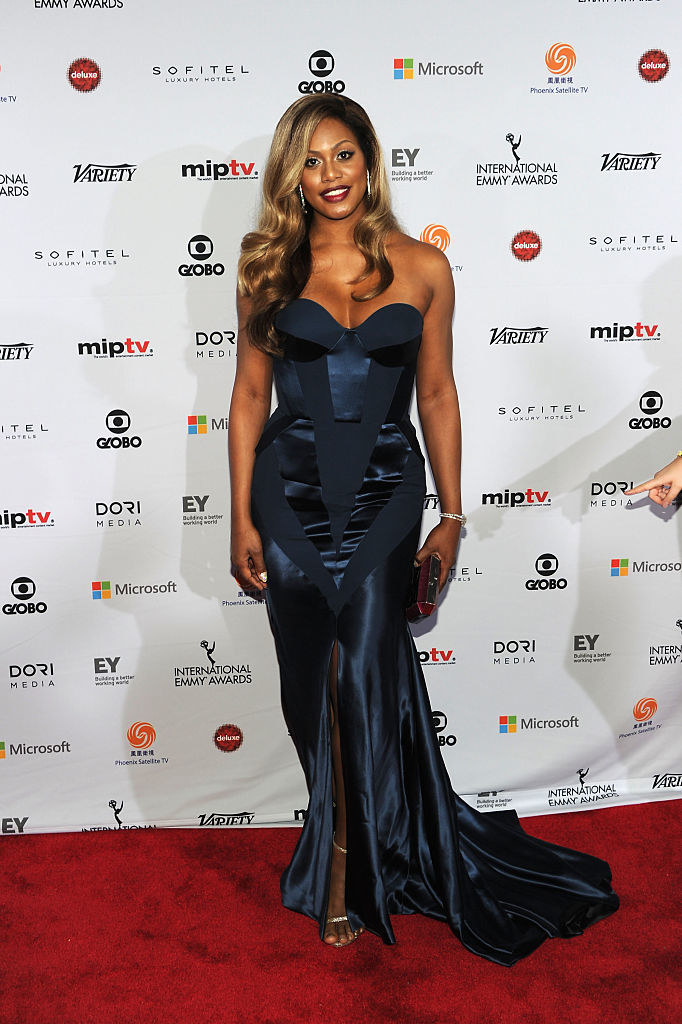 Laverne in a mermaid tuxedo-like sweetheart neckline strapless gown with a slit and corset like top with satin panels and skirt