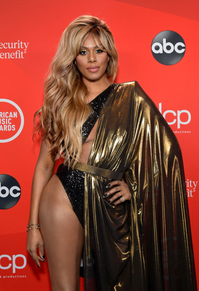 Laverne Cox in a one shoulder dress, with the left side a cape-like flowing long sleeve dress and the left side as a glitter cutout leotard