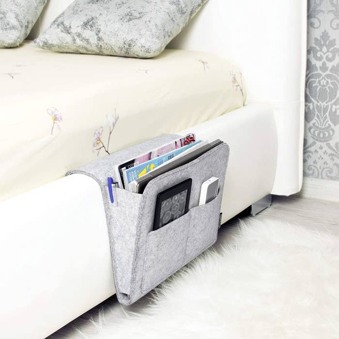 bedside caddy attached to side of bed filled with magazines, tablets, pens