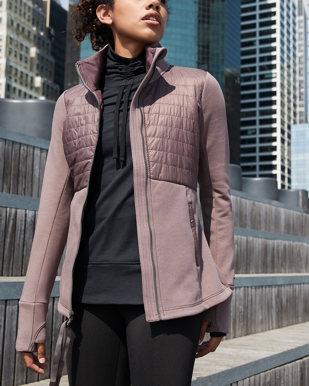model wearing the zip-up jacket with quilted portion on the top half, and zipper on either side