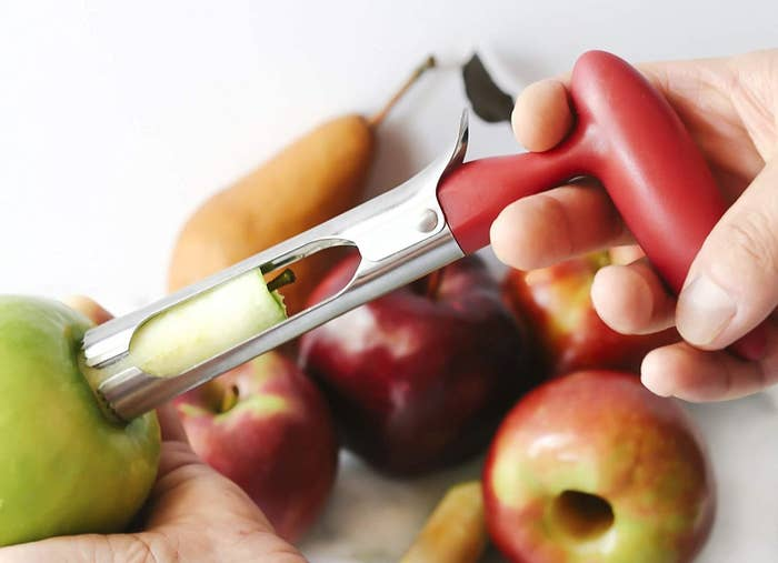person coring an apple with the device