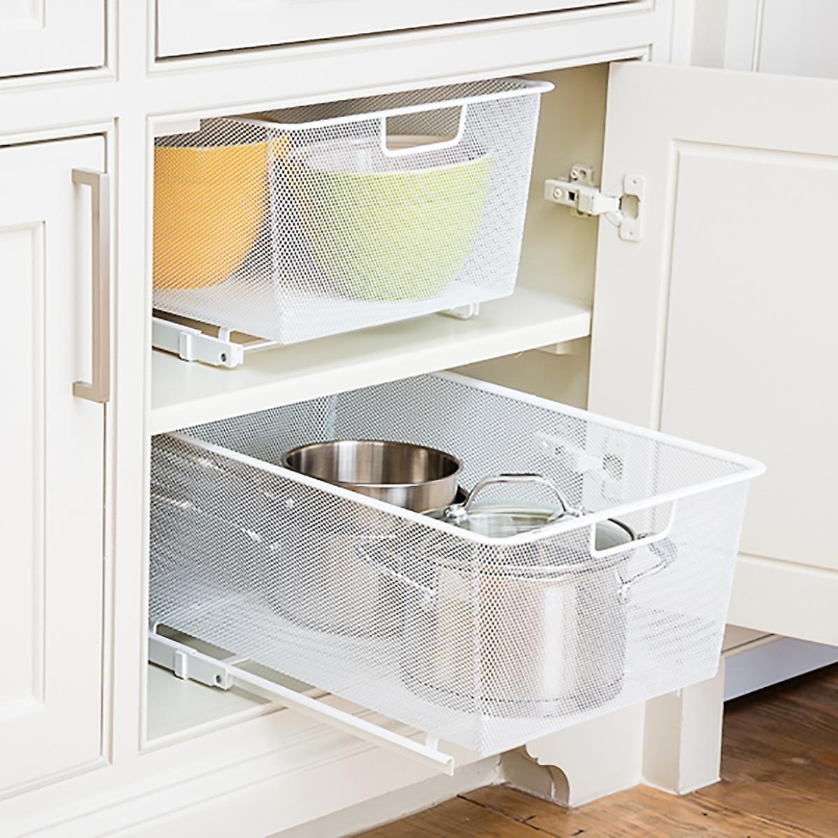 Sliding drawer placed in cabinet with various pots and pans inside