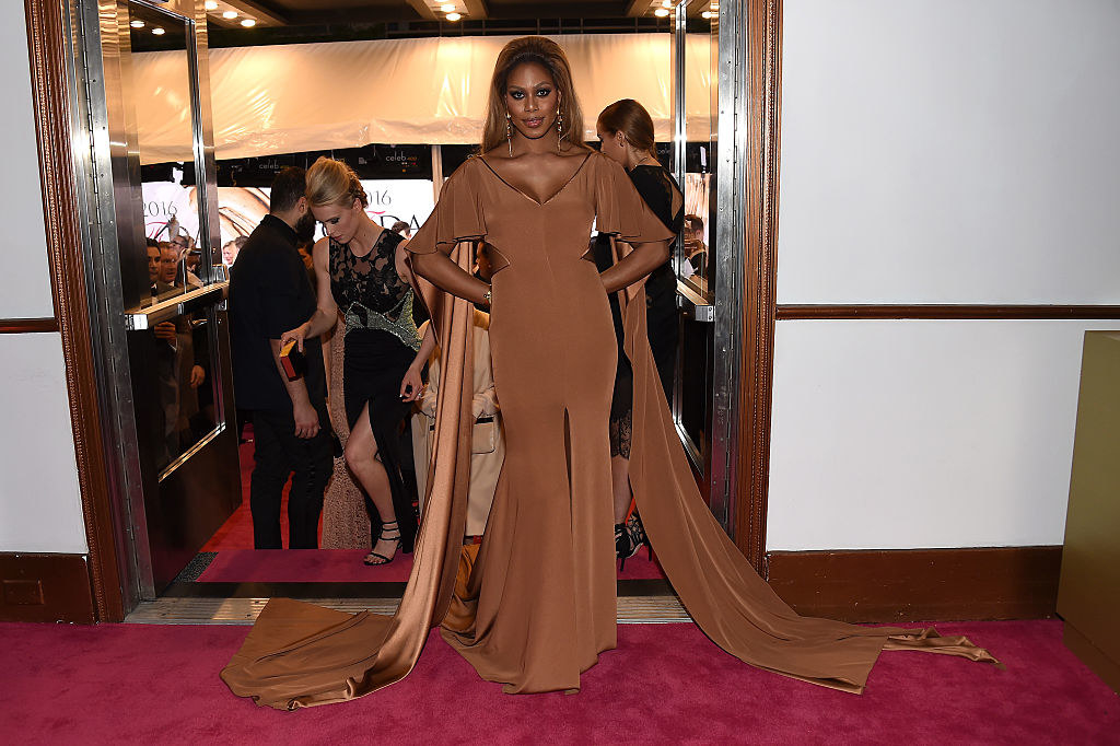Laverne in a silky dress with elbow-length fluttery sleeves, a wide V neck, a slight mermaid flare at the bottom, and a cape behind her shoulders