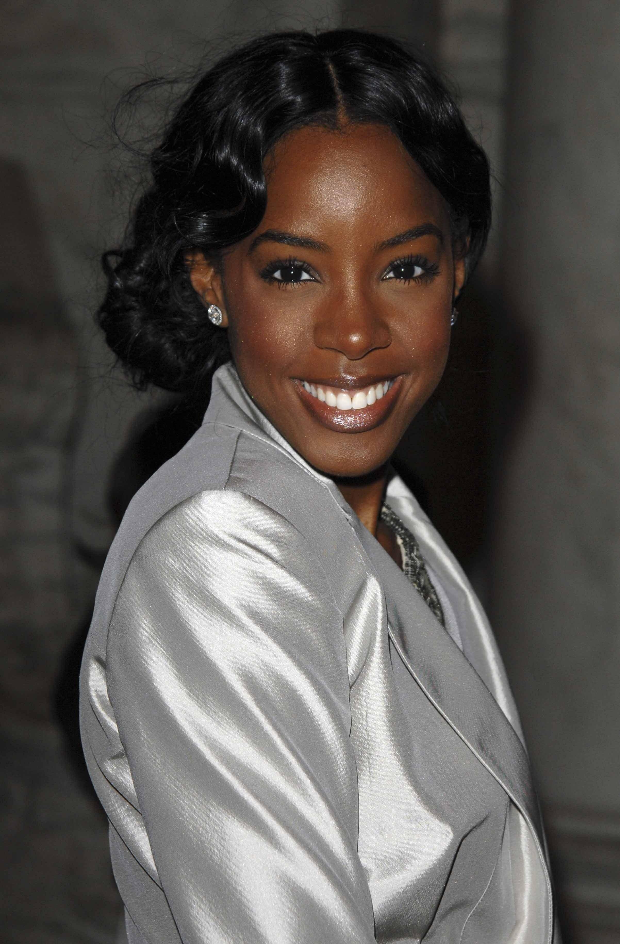 Kelly Rowland smiling wearing a silver blazer