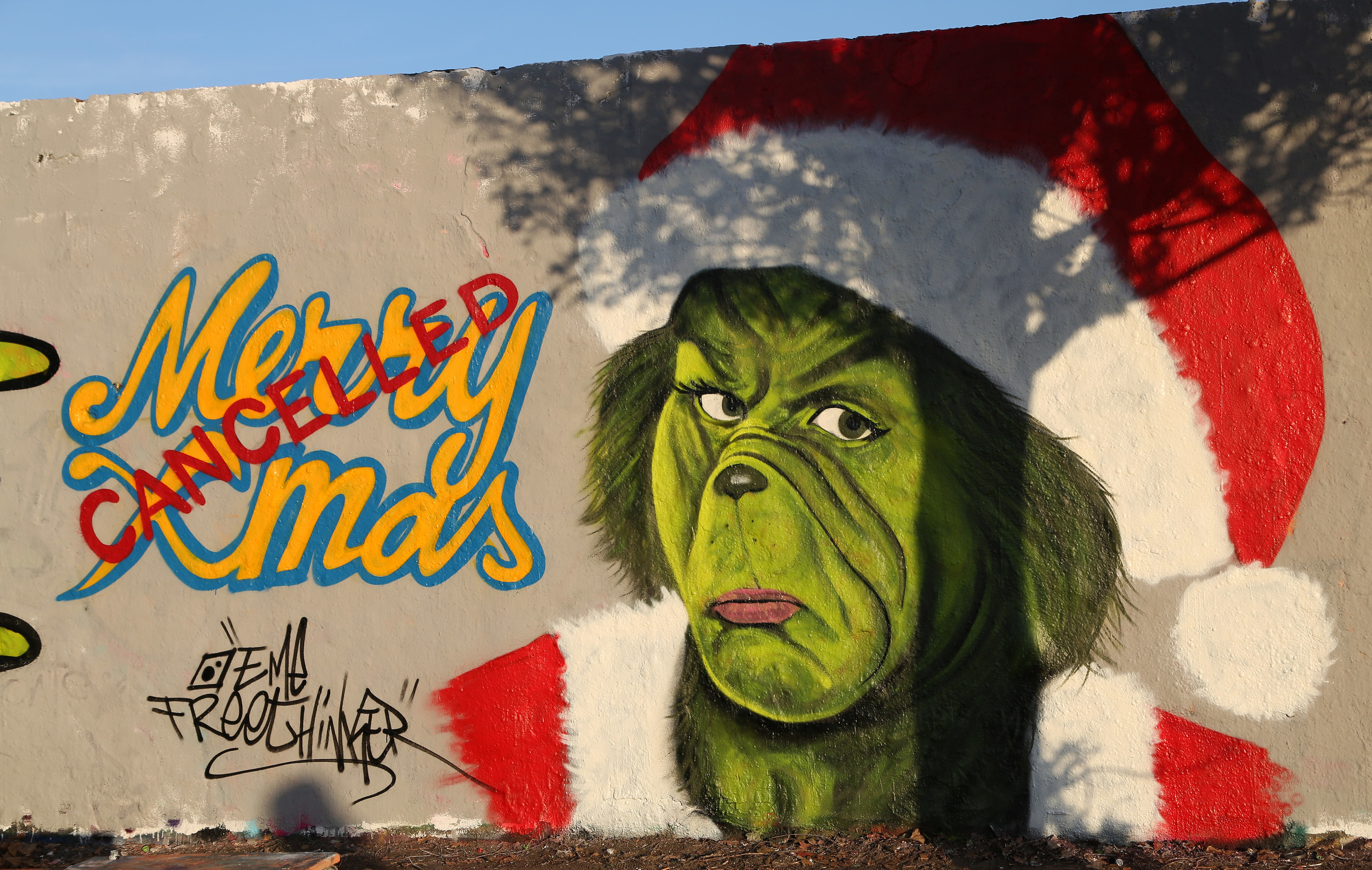 A graffiti drawing of the Grinch on a wall