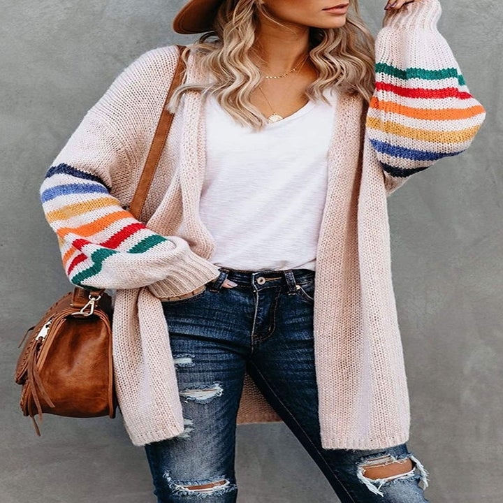 A model wearing the long light pink cardigan with colorful stripes on the voluminous sleeves