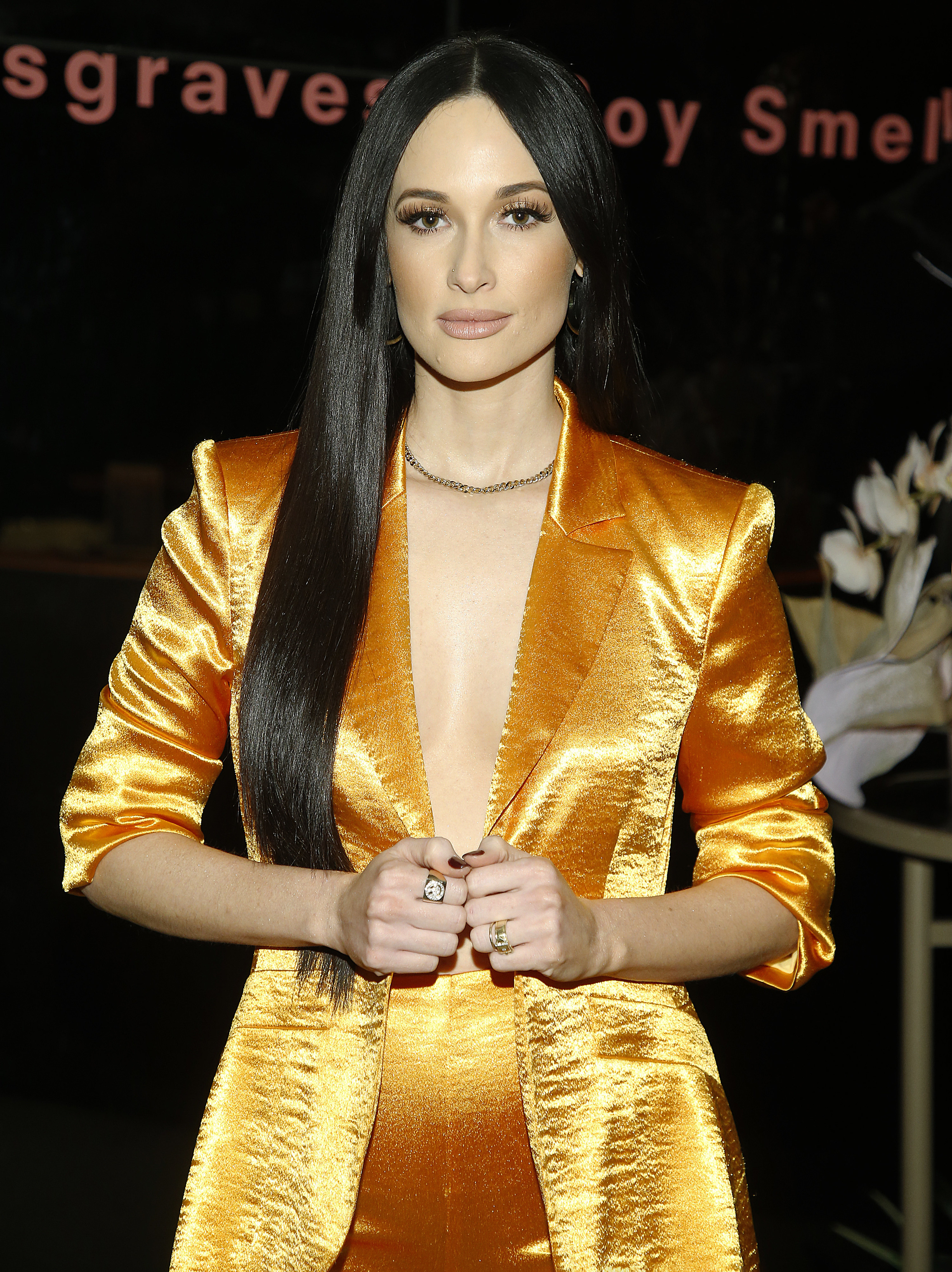 Kacey at a even wearing a gold suit