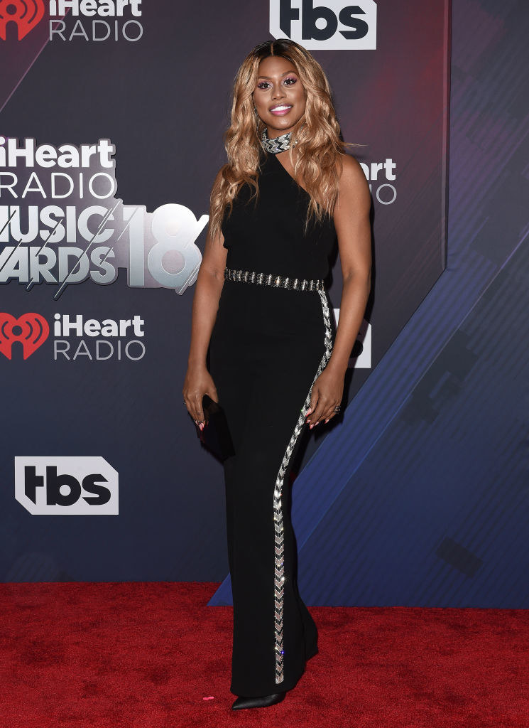 Laverne in a one-shoulder jumpsuit with chevron going along the belt and in a ribbon down the side as well as on a choker halter at the top