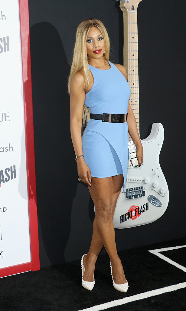 Laverne in a short tight high neck sleeveless minidress with a shiny belt at the high waist and an assymetric bottom