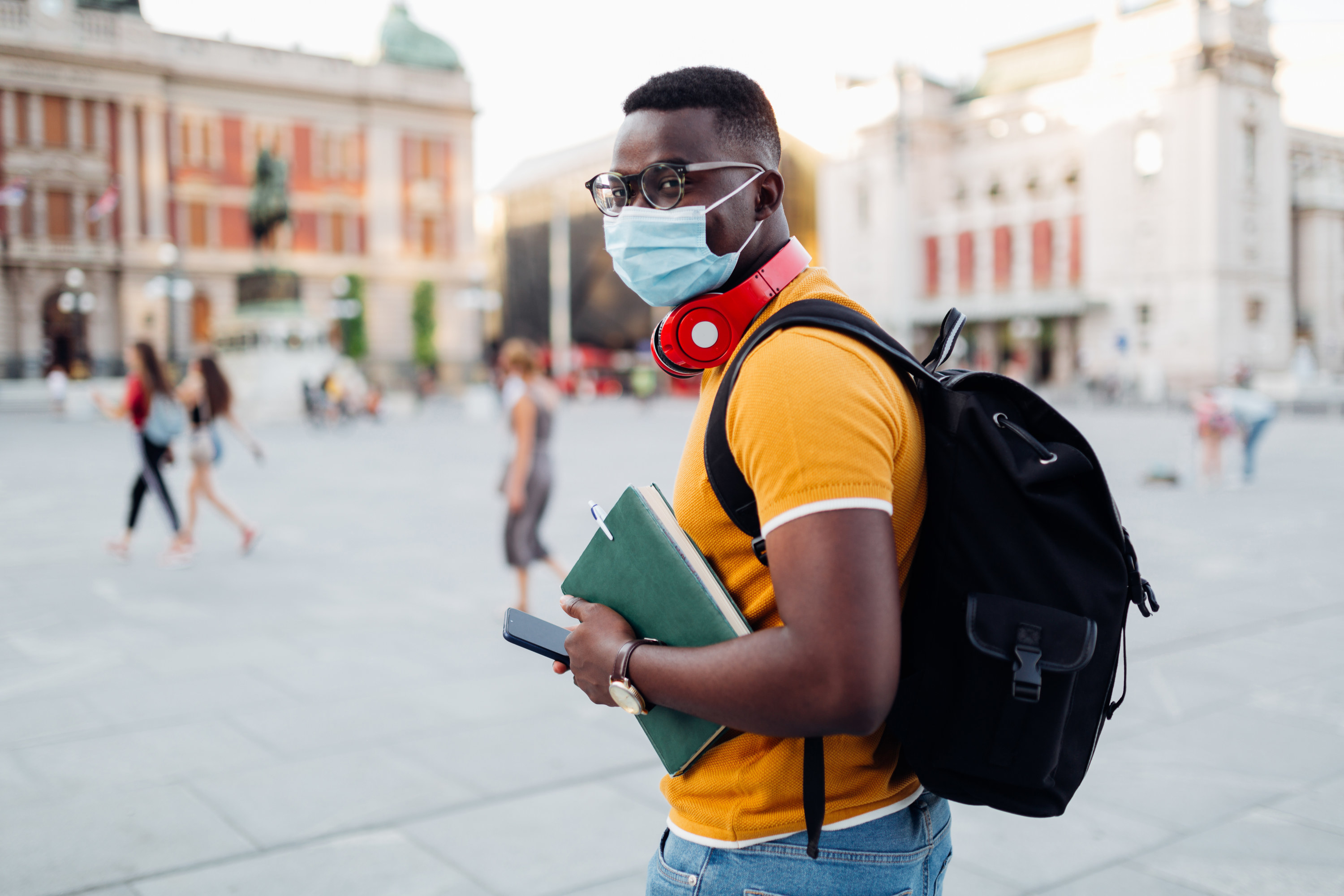 student on college campus wearing a mask