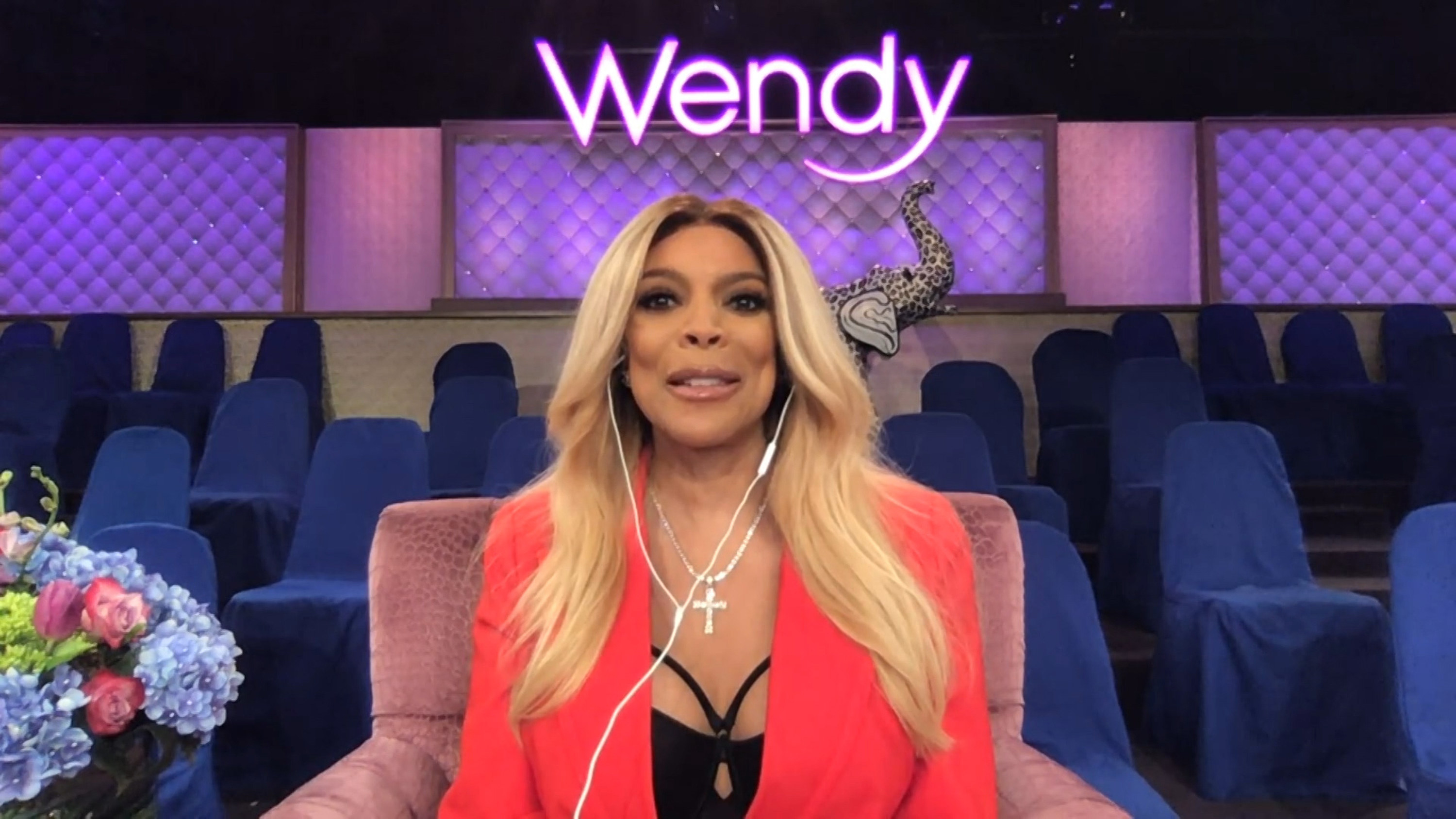 Wendy Williams in a bright orange pink jacket sitting alone in the audience of her show with headphones on