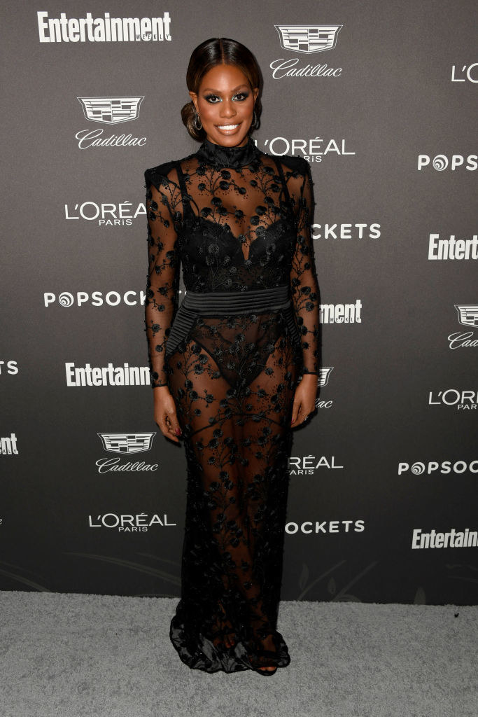 Laverne in a long sheer turtleneck long sleeve dress with flowers embroidered on the sheer fabric and a deep v corset style leotard underneath