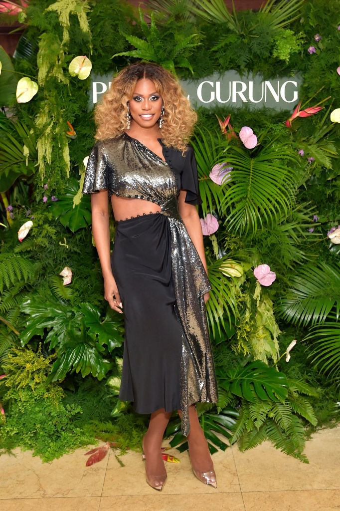 Laverne in a patchwork style midi dress with satin and glitter fabric, short flutter sleeves, and a triangle cutout at the waist