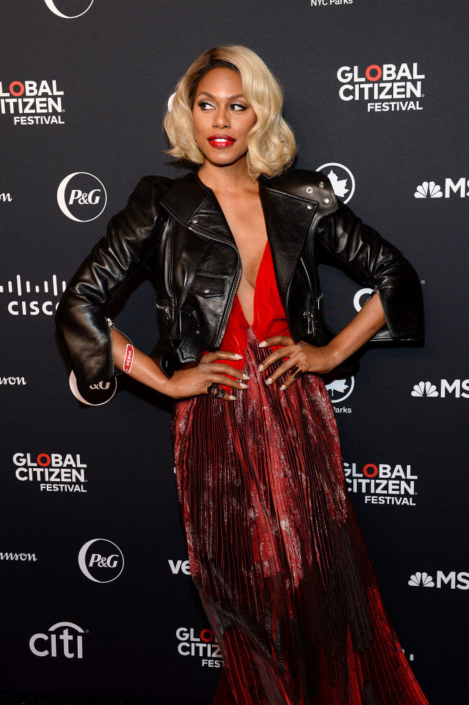 Laverne in a deep v satiny dress with a thin pleated skirt with a cropped leather moto jacket over it