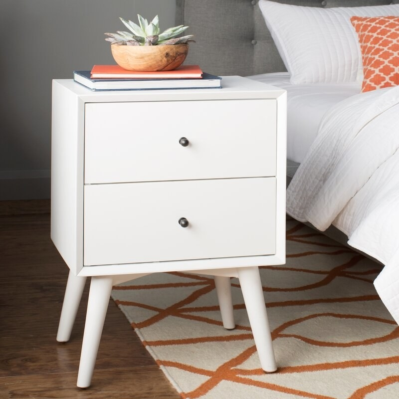 The nightstand in white, with two drawers with small knob pulls and four splayed legs