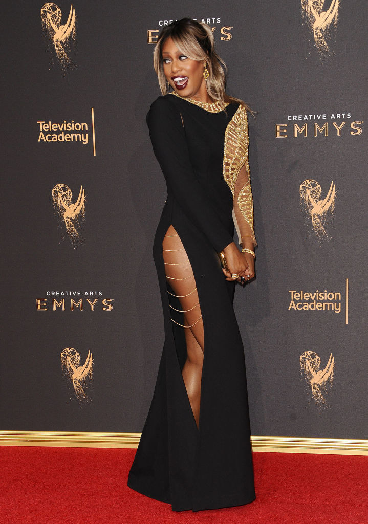 long sleeve dress with slight flare bottom, a really high slit with metallic chains at the top of it tying the sides to each other, and long sleeves with one sleeve made of mesh and geometric metallic embroidery that also lines her neck