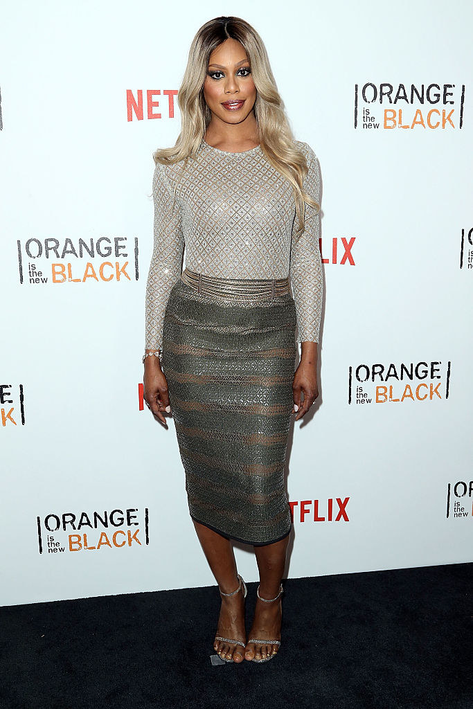 Laverne in a tight high scoop neck long sleeve metallic diamond top with a metallic belt and mid-length pencil skirt with sheer stripes