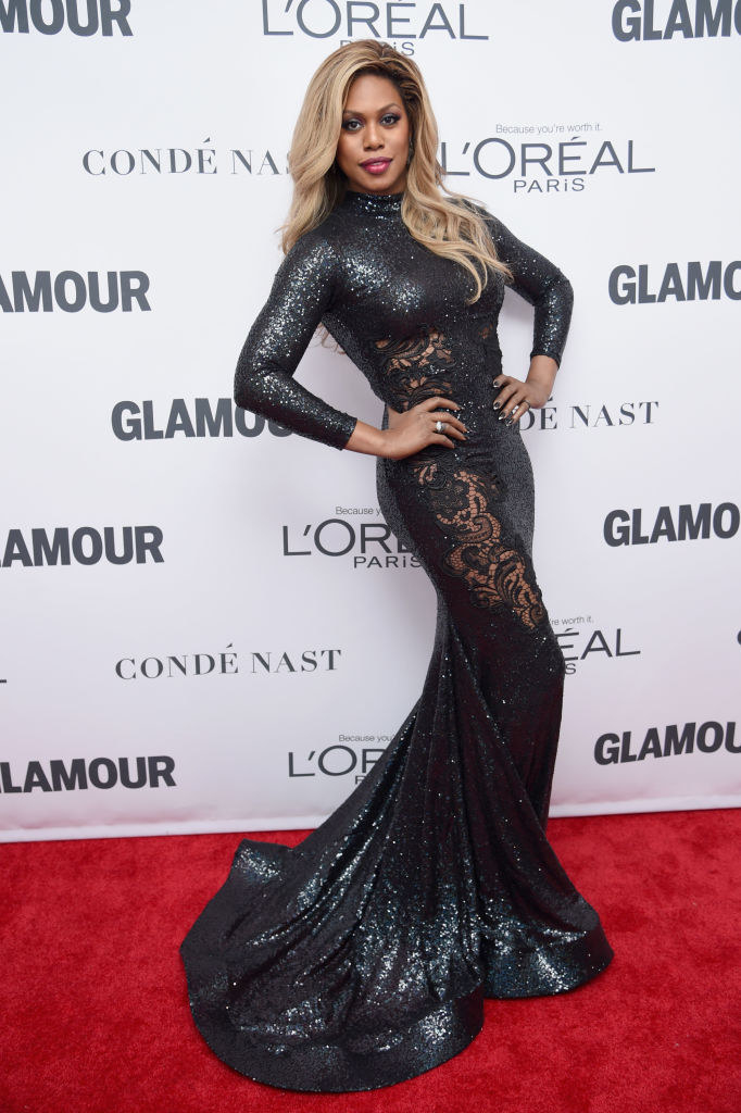 Laverne in a tight mermaid glitter gown with long sleeves and a turtleneck, with a large lace cutout going down the side