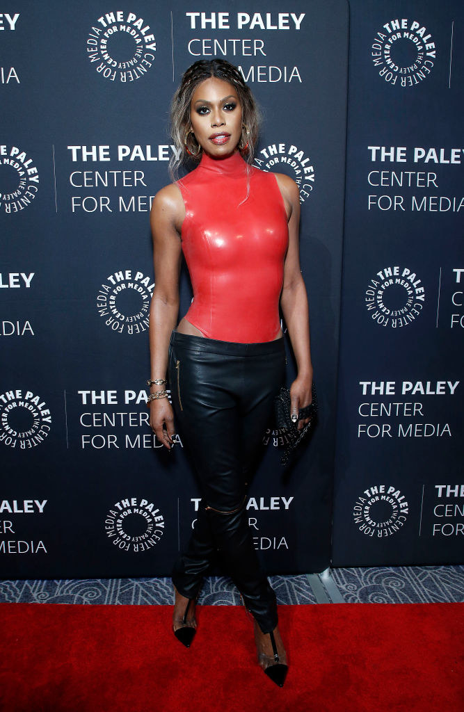Laverne in a tight latex turtleneck sleeveless bodysuit with low waist tight leather pants underneath