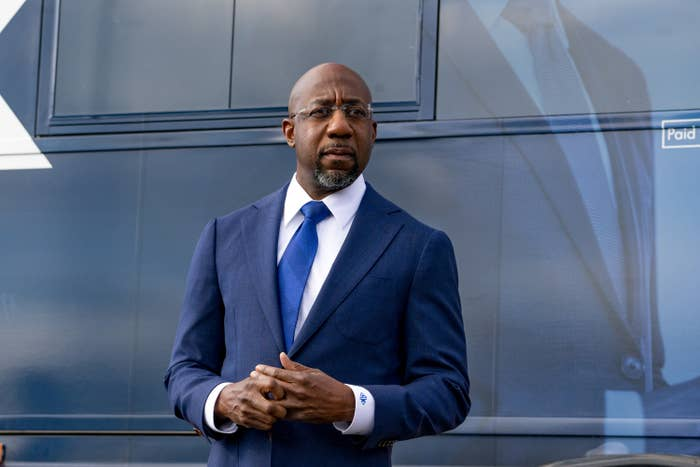 Raphael Warnock is shown wearing a suit and tie