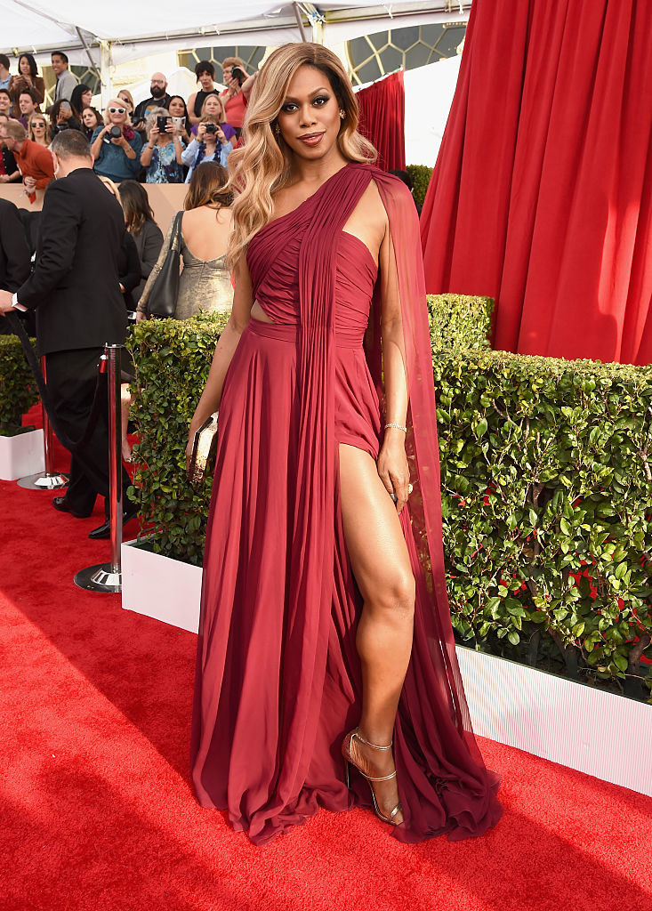 Laverne in a ruched chiffon gown with a loose skirt with a high slit, a one-shoulder top that goes into a slight cape over the shoulder, and a tiny cutout at the waist