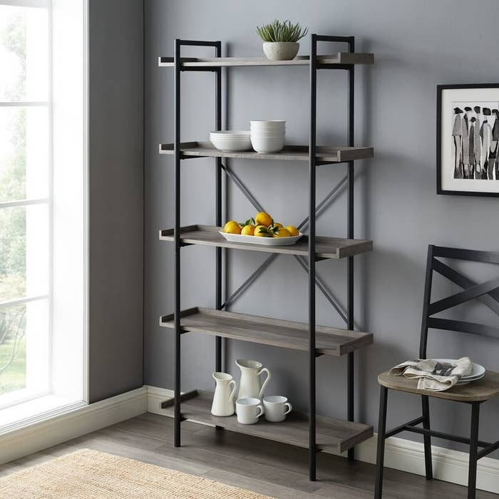 The bookcase in gray, with five gray wood shelves, and black pipe-style metal framework