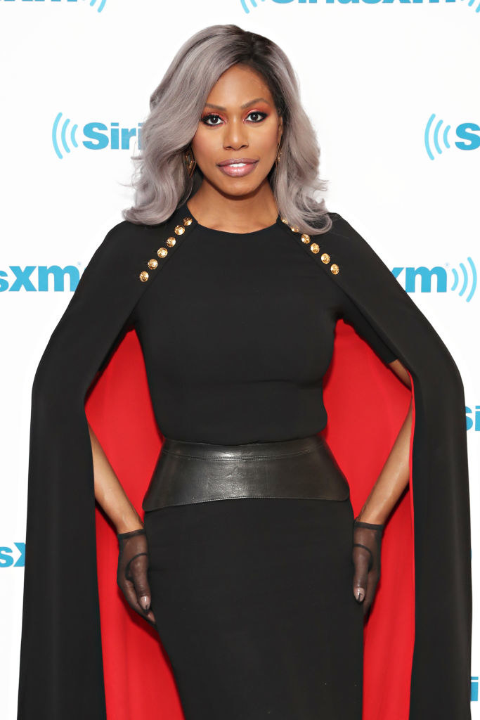 Laverne in a cape dress with metallic buttons at the top of the cape and a thick leather belt at the waist of the dress