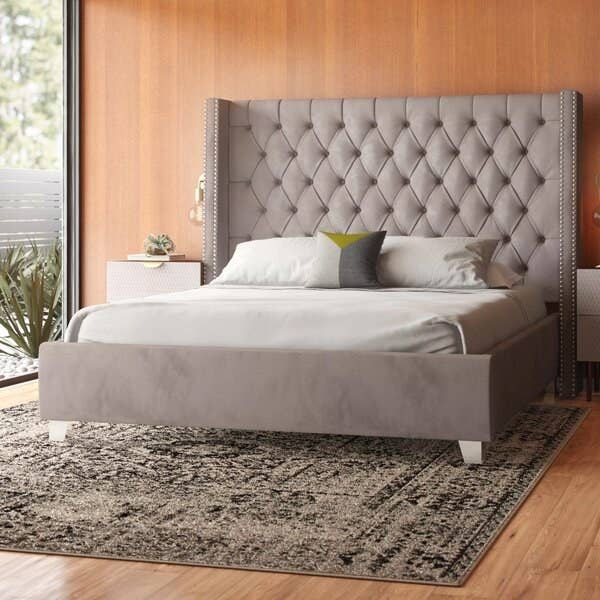 The bed frame in gray, with a tall headboard with tufting and slightly forward-curved, wingback-style edges