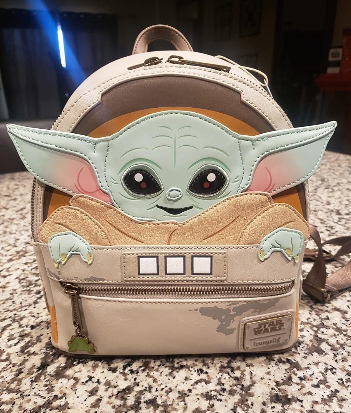 The backpack shaped like Baby Yoda in his pram