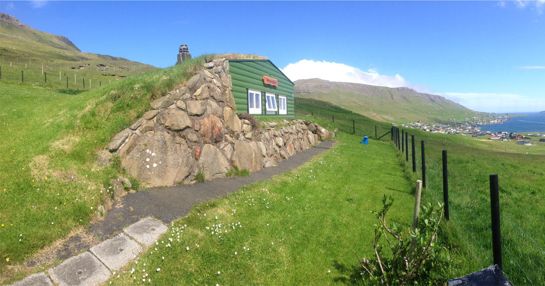 A small green hut built into a rolling rocky and green hill