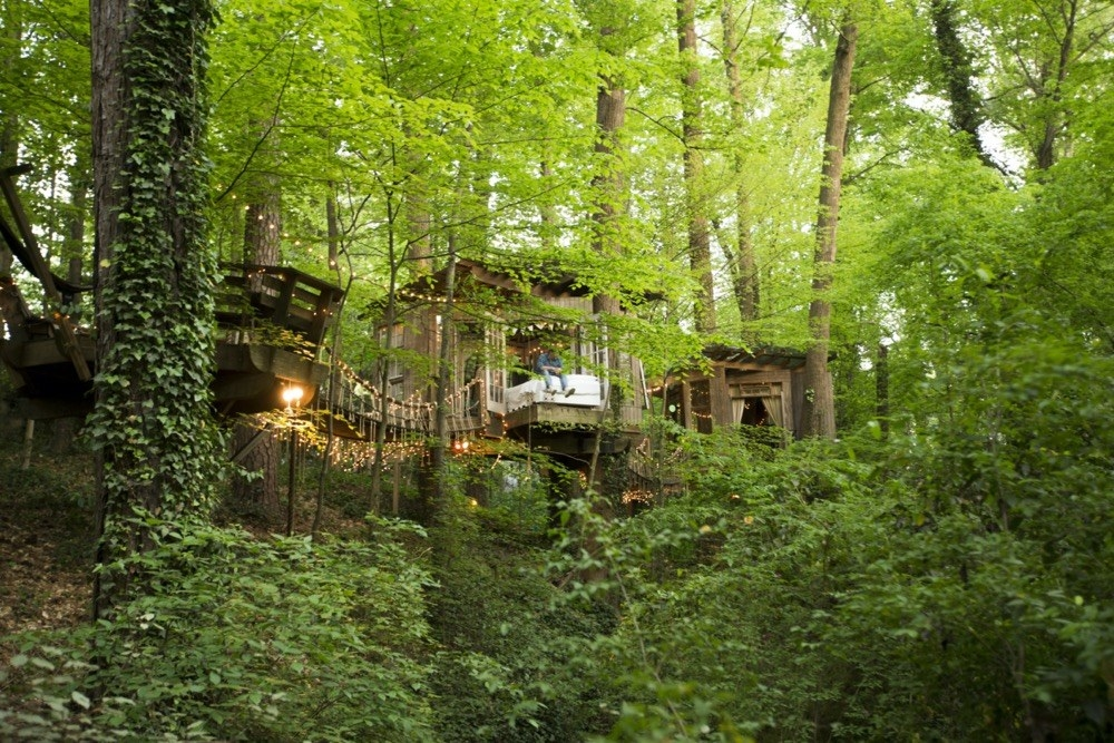 A whimsical wooden room built into the trees, accessible by swing bridge and decorated with fairy lights