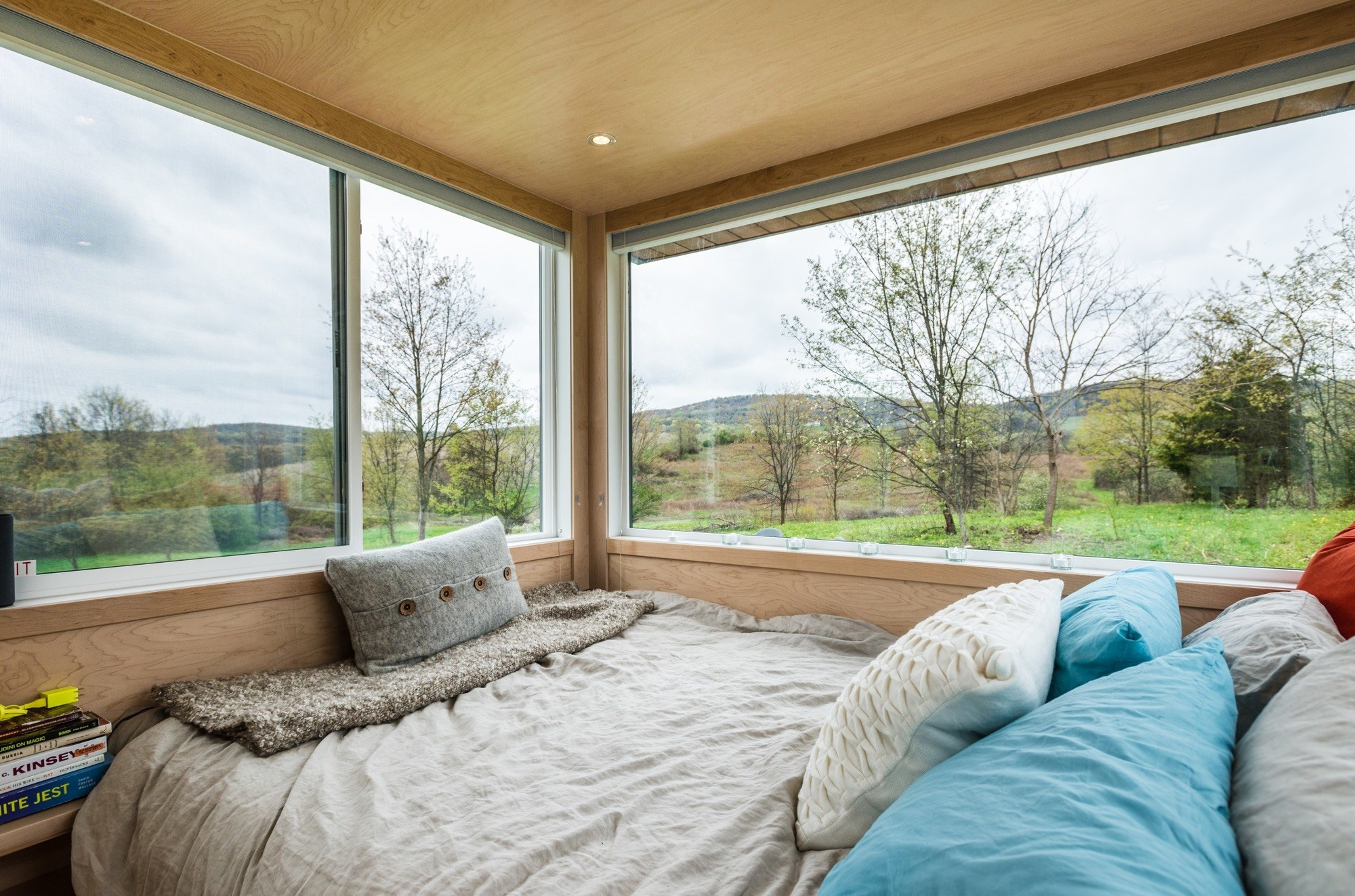 The interior of a glass-walled cabin with a bed covered in pillows. Out the window is nothing but trees