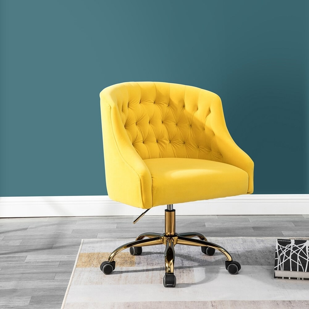 The chair in yellow, which has a barrel-style back, and gold-tone swivel base with rollers