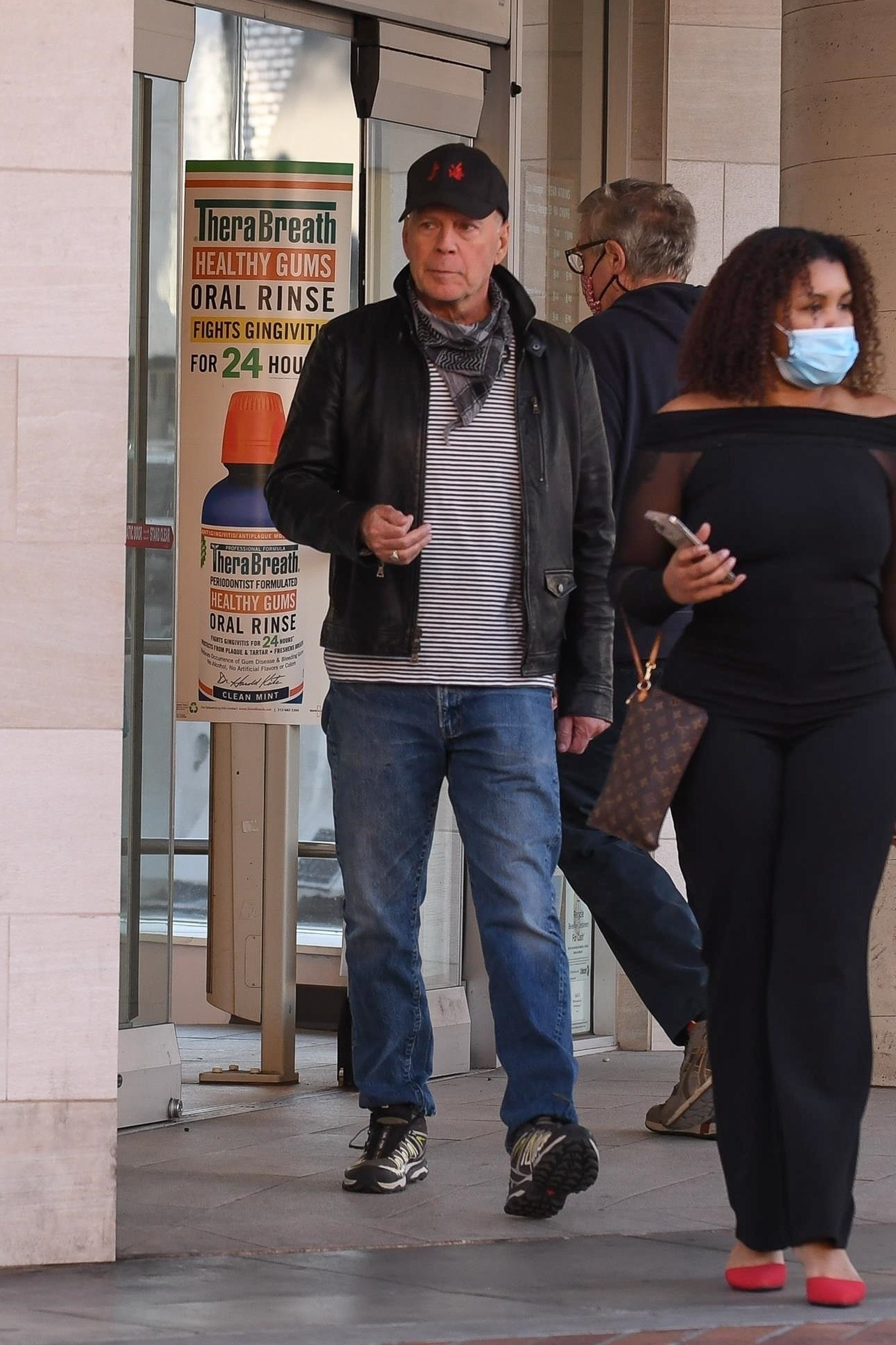 Bruce Willis is spotted walking around outside without wearing a mask while other people wear their masks