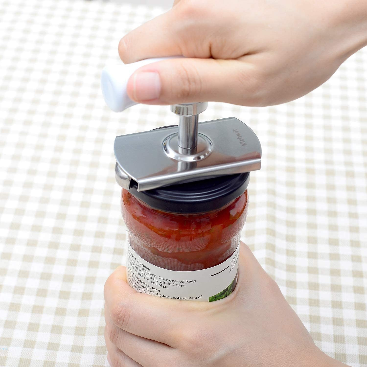 person using the lid opener to twist open the lid of a jar