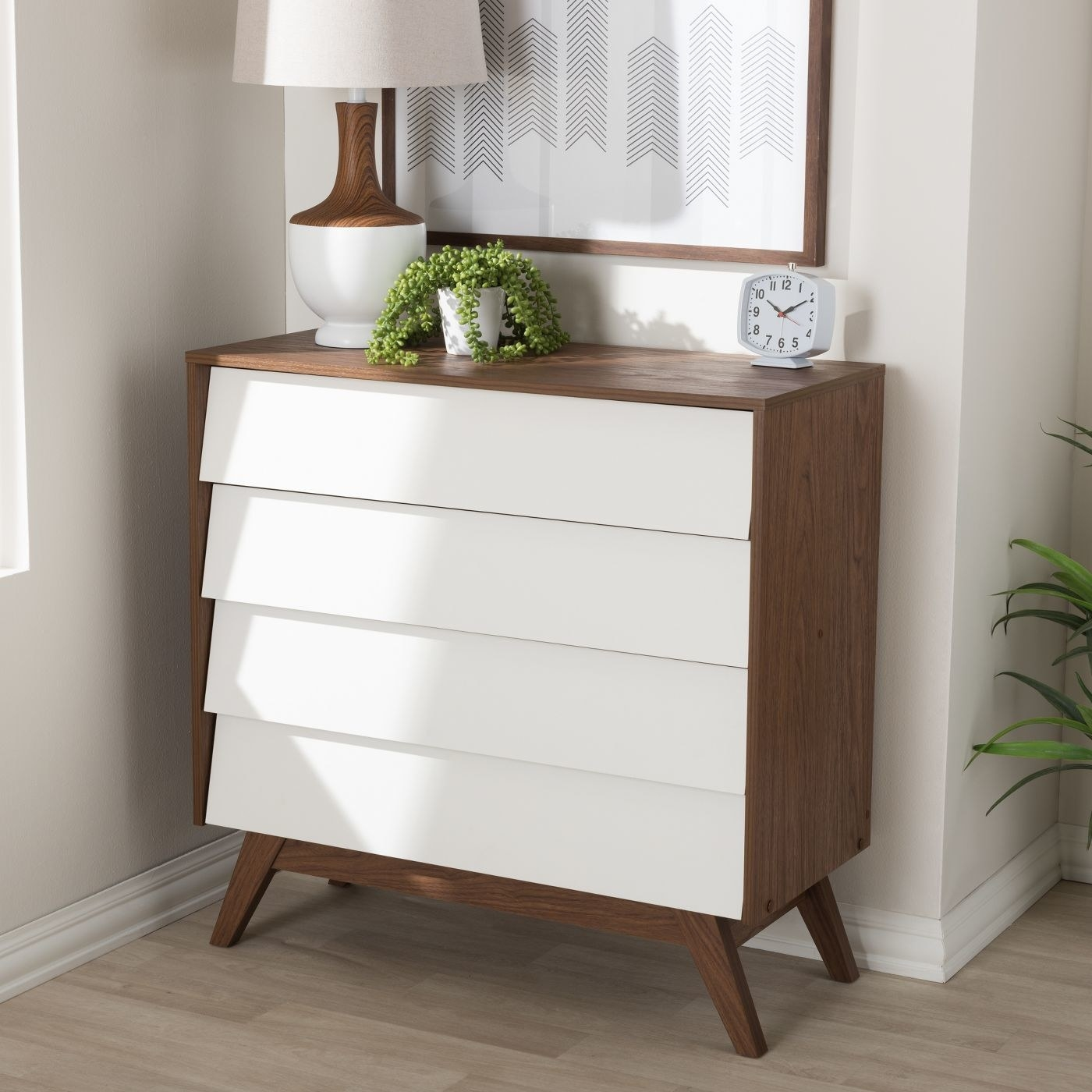 A four drawer dresser with a two tone finish in walnut and white